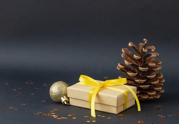 Fundo preto de natal com cone de caixa de presente e enfeite de natal