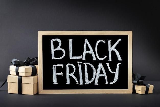 Fundo preto de sexta-feira com inscrição no quadro-negro e caixas de presente