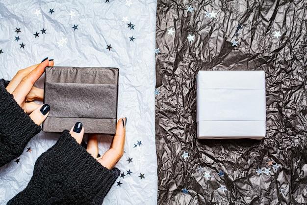 Fundo preto e branco de natal com caixas de presente e estrelas de confetes. conceito de natal.