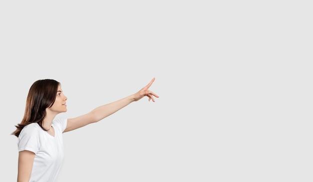 Fundo promocional. mensagem do anúncio. mulher curiosa isolada apontando para cima no espaço neutro da cópia.