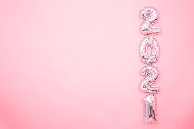 Fundo rosa claro com balões prateados de ano novo em forma de números no lado direito, conceito de ano novo