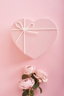 Fundo rosa com flores e caixa de presente