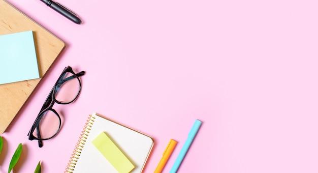 Fundo rosa com o bloco de notas, óculos de escritório, caneta, lugar para texto. conceito de tendência.