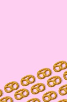 Fundo rosa com pretzels vista superior padrão de pretzel