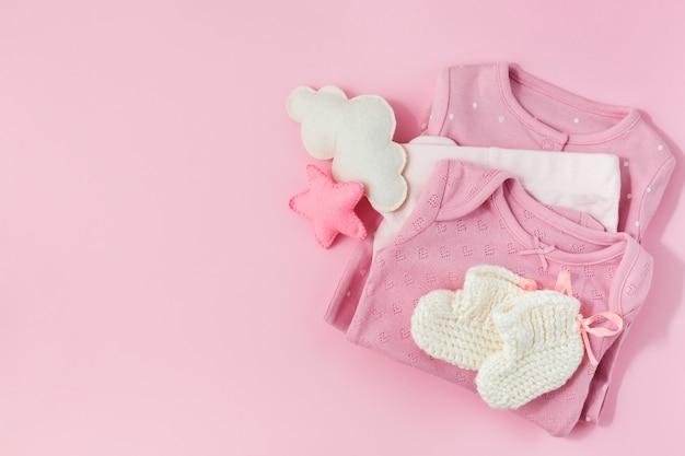 Fundo rosa com roupas, meias e brinquedos para uma menina recém-nascida.