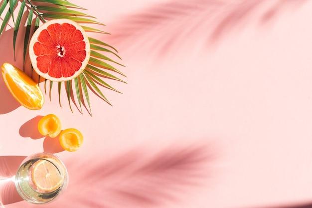 Fundo rosa com sombras verão bebe água com limão frutas frescas com folha de árvore tropical