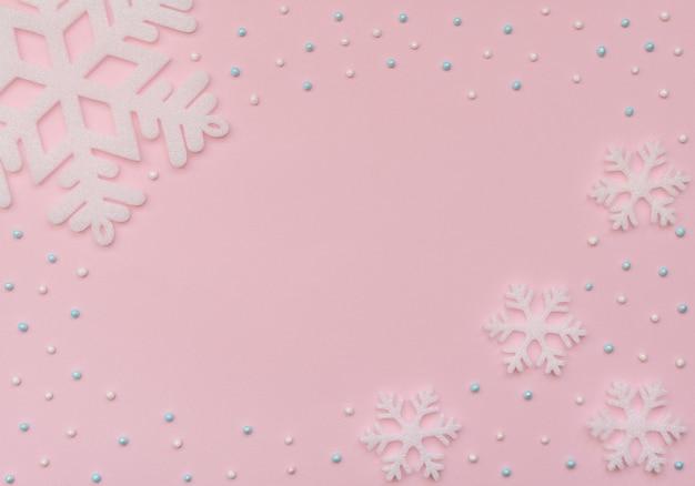Fundo rosa de natal com flocos de neve brancos e miçangas. cartão de ano novo.