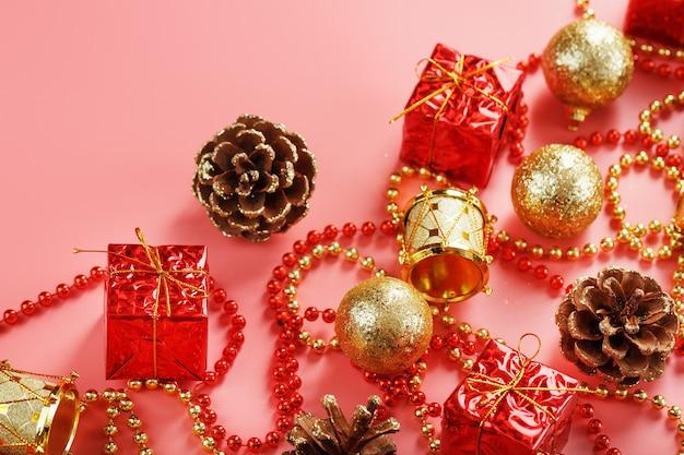 Fundo rosa de natal ou ano novo com decorações vermelhas e douradas para árvore de natal com espaço livre. a vista do topo. humor de ano novo.
