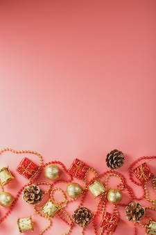 Fundo rosa de natal ou ano novo com decorações vermelhas e douradas para árvore de natal com espaço livre.
