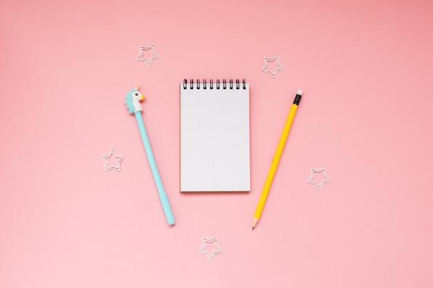 Fundo rosa e material escolar amarelo
