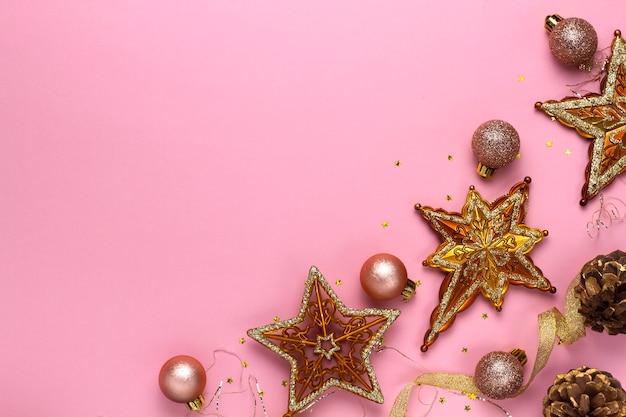 Fundo rosa feriado de natal com brinquedos dourados
