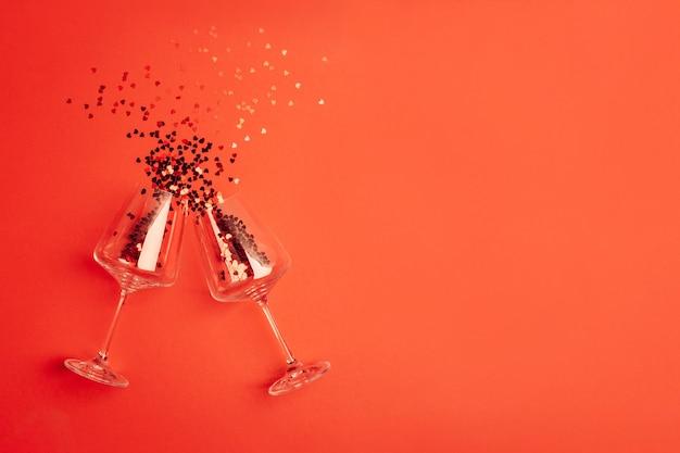 Fundo rosa feriado romântico com taças de vinho e glitter vermelho em forma de coração. placa decorativa para são valentim com espaço para texto. tema de amor.