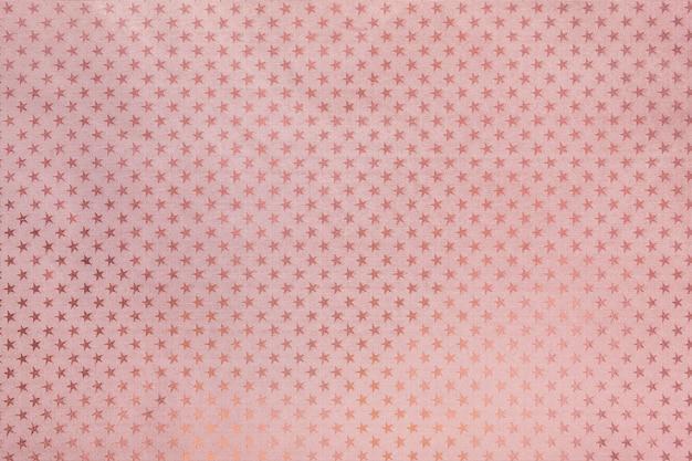Fundo rosa ouro de papel de folha de metal com um padrão de estrelas