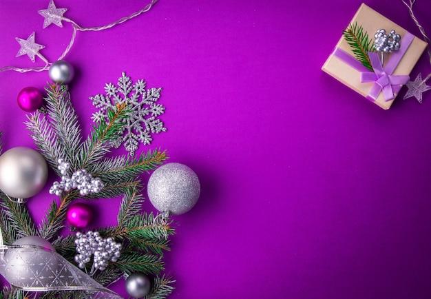 Fundo roxo de natal com um presente, abeto, brinquedos e arcos