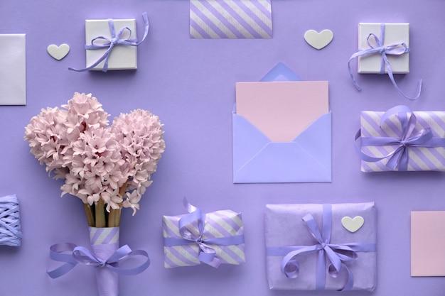 Fundo roxo primavera com flores jacintos rosa, caixas de presente embrulhadas e corações decorativas, cópia-espaço
