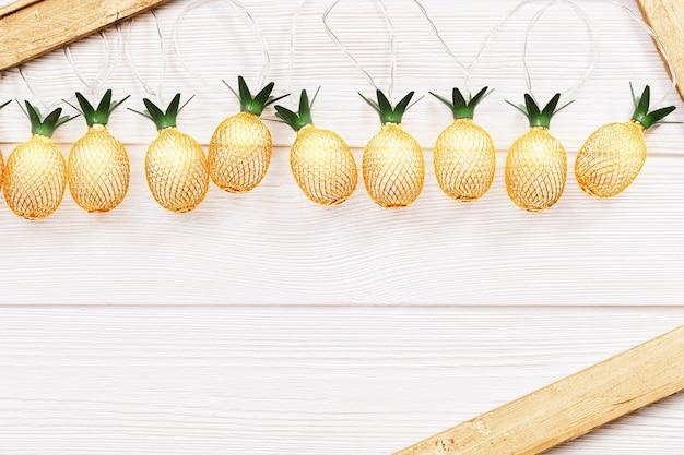 Fundo rústico de natal com luzes de corda como abacaxis dourados
