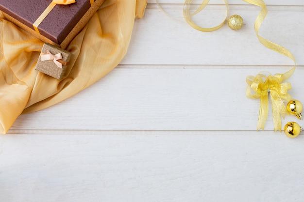 Fundo superior branco da textura da tabela com toalha de mesa dourada e natal decorativo.