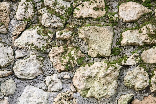 Fundo, textura - alvenaria áspera musgosa de pedra natural em bruto