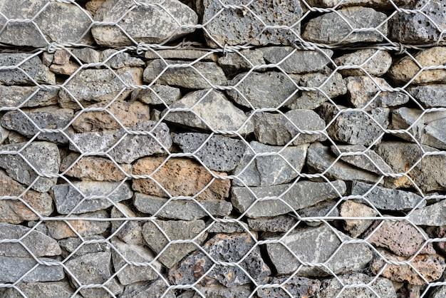 Fundo texturado de gabion, parede de rocha com cerca de malha de arame.