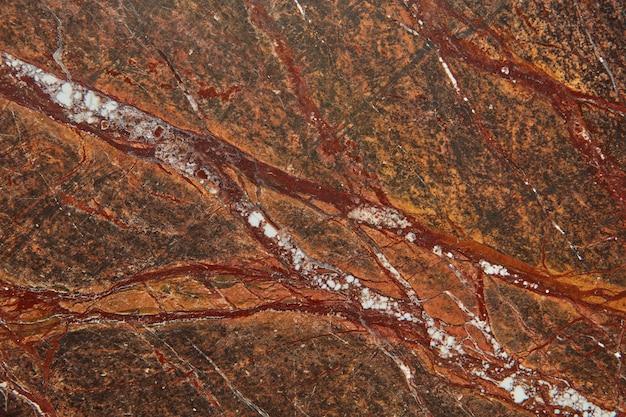 Fundo texturizado abstrato de pedra de mármore com veias brancas e vermelhas, copie o espaço para sua criatividade. fundo natural para decoração de interiores.