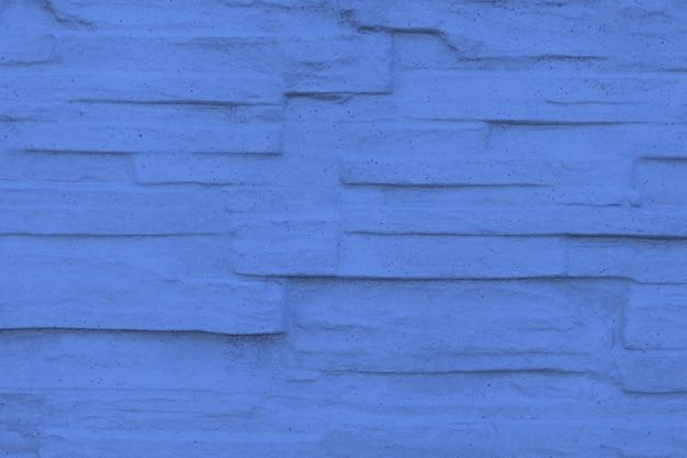 Fundo texturizado de parede de tijolo de pedra tonificado na cor azul clássica na moda do ano 2020
