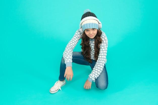 Fundo turquesa de garoto legal. música para a lista de reprodução de inverno. música de inverno favorita. menina gosta de música favorita. humor da música. criança pequena malha camisola e chapéu. ela está ouvindo música em fones de ouvido.