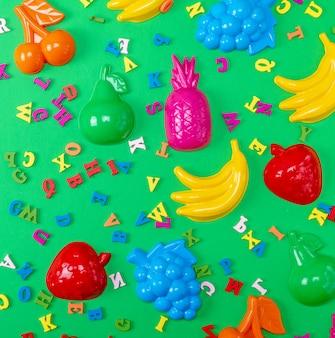 Fundo verde com brinquedos de plástico para crianças e letras multicoloridas de madeira