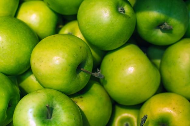 Fundo verde das maçãs completamente das laranjas. maçã verde fresca no mercado.