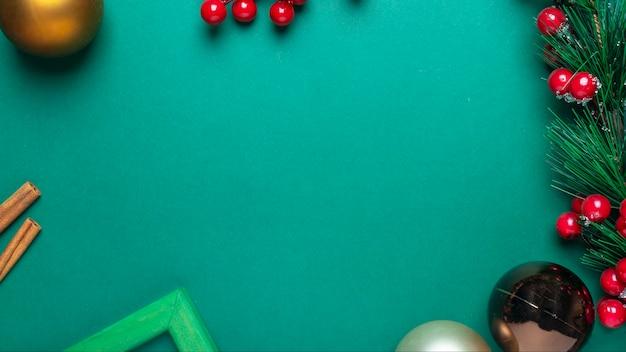 Fundo verde de natal com moldura de ramo de abeto, bagas vermelhas, canela, enfeites de natal ou bolas e lugar para texto ou espaço de cópia.