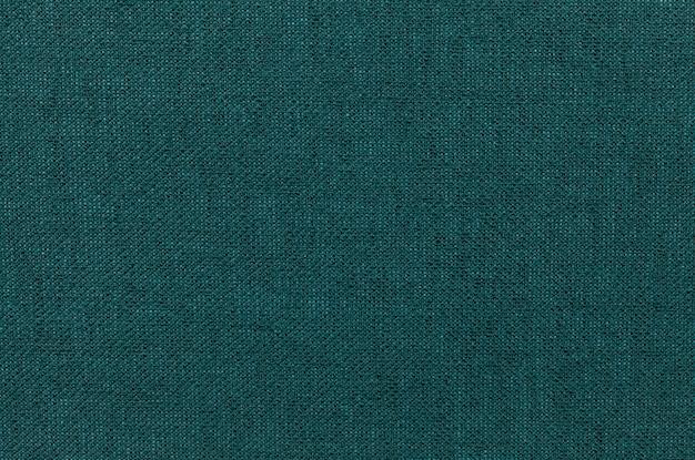 Fundo verde escuro de um material têxtil.