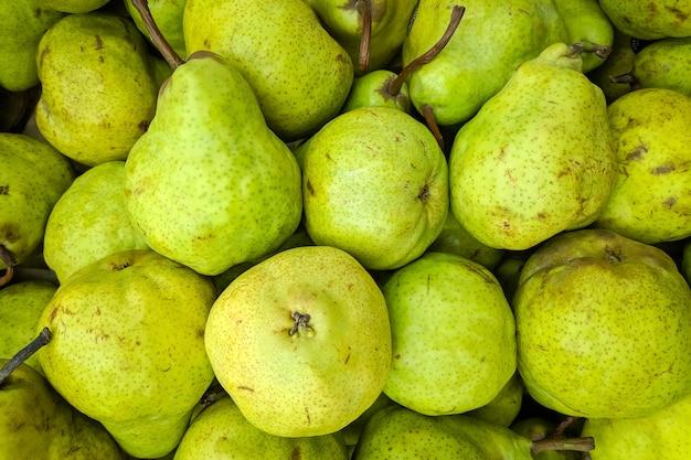 Fundo verde pêra. variedade de peras frescas cultivada na loja.