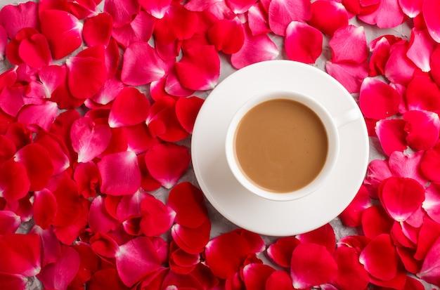 Fundo vermelho das pétalas cor-de-rosa e uma xícara de café.