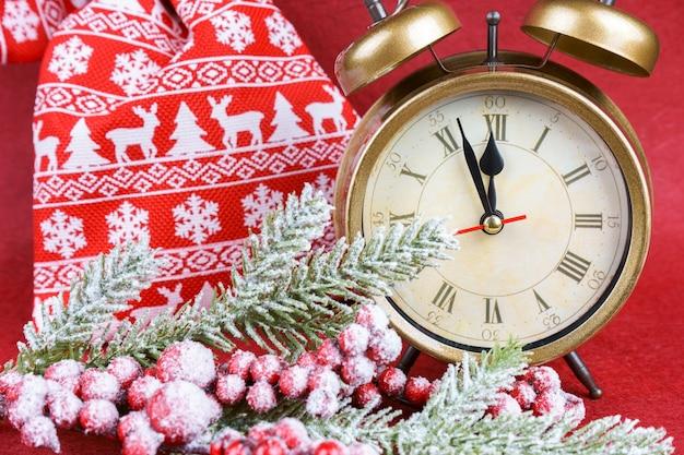 Fundo vermelho de ano novo com árvore de natal de abeto de neve, despertador e sacola de presente. o relógio vermelho conta até doze.