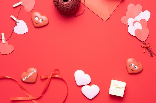 Fundo vermelho de dia dos namorados com decorações de forma de coração, presente e fitas. vista de cima. composição plana leiga