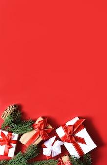 Fundo vermelho de natal com abeto e presentes com fita. decoração de reveillon.