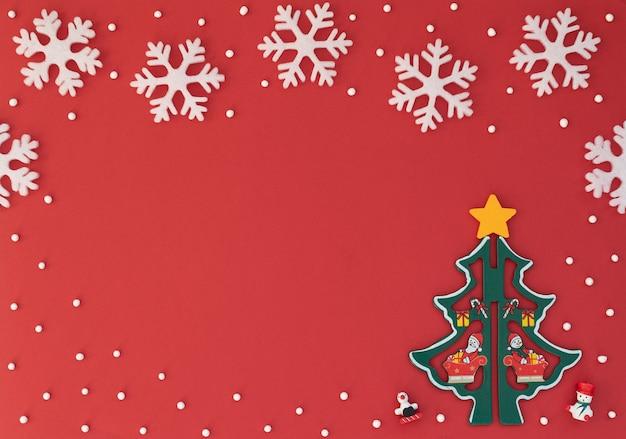 Fundo vermelho de natal com árvore de natal de madeira e flocos de neve brancos. cartão de ano novo. estilo liso leigo.