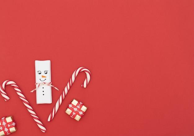 Fundo vermelho de natal com boneco de neve, bastões de doces e caixas de presente com fita vermelha. estilo liso