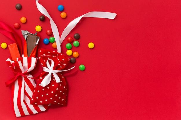 Fundo vermelho de natal com sacos de doces e espaço de cópia. presentes doces de ano novo