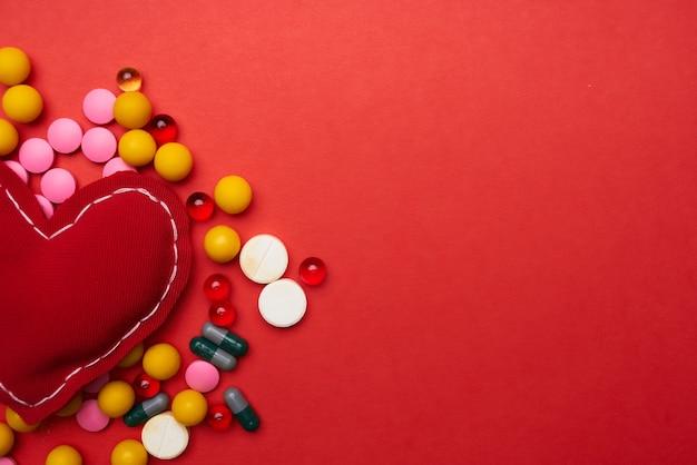 Fundo vermelho de tratamento de saúde de comprimidos multicoloridos