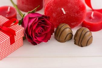 Fundo vermelho do dia de Valentim com rosas vermelhas e chocolate em uma tabela de madeira branca.