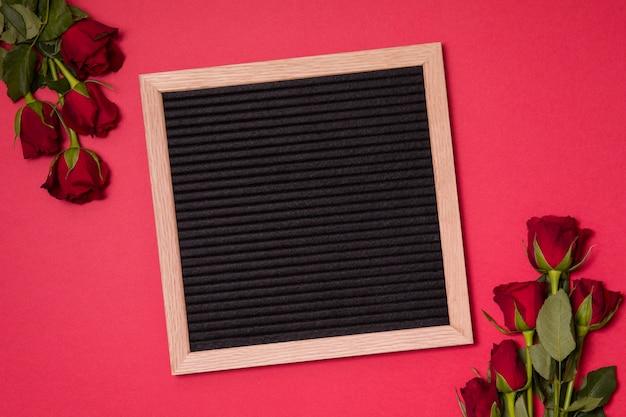 Fundo vermelho do dia de valentim, placa de letra vazia com rosas vermelhas.