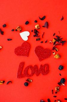 Fundo vermelho do dia dos namorados com corações de madeira e a palavra amor. lugar para inscrições, publicidade