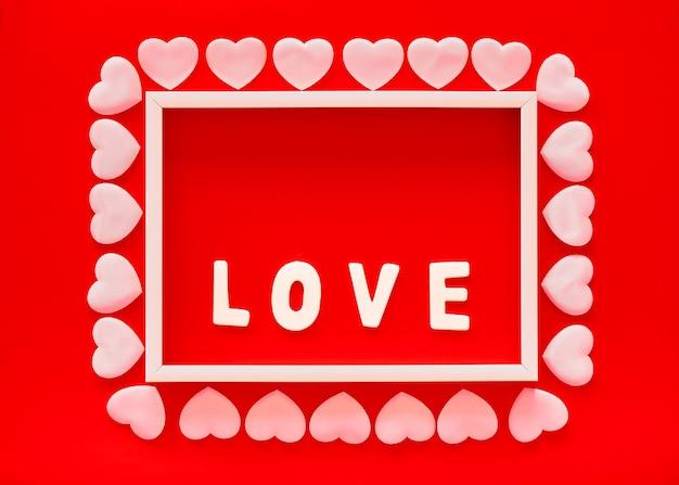 Fundo vermelho do dia dos namorados com moldura branca, a palavra amor e corações rosa. dia das mães, cartão comemorativo de 8 de março