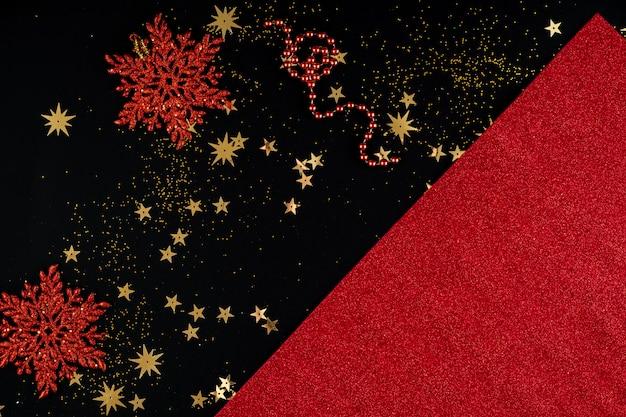 Fundo vermelho e preto festivo de natal com lantejoulas e flocos de neve
