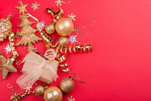Fundo vermelho festivo bonito com brilhos e brinquedos de natal dourado.