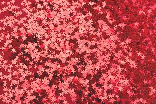 Fundo vermelho festivo bonito. muitas estrelas metálicas em forma de confete. ano novo e cristo