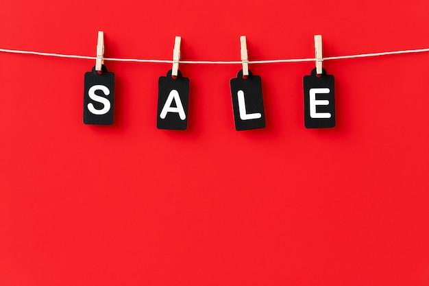 Fundo vermelho para vendas com etiquetas pretas penduradas em prendedores de roupa