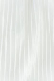 Fundo vertical de tecido plissado branco localizado na vertical. esquema de verão feminino de elegância.