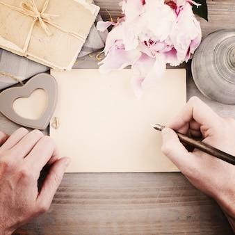 Fundo vintage com caneta de mãos masculinas e homem de papel escrevendo carta de amor