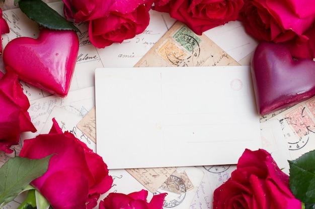 Fundo vintage com moldura de corações e rosas frescas